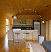 The wooden floor, ceiling and walls of this contemporary log cabin create an homogenous interior