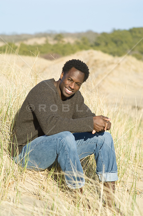 Young good looking African american man in a sweater sitting on a grassy hillside In Amagansett, NY