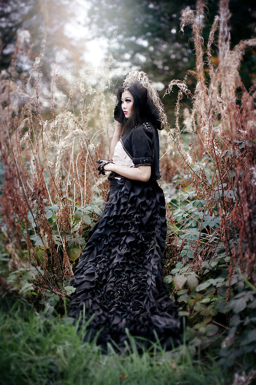 a woman in black hood and gothic style clothing stood amongst tall plants in a forest