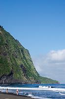 Two women walk along the black sand beach at Waipi'o Valley, Hamakua District, Island of Hawai'i.