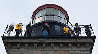 A view of the outside of the top of Point Sur Light Station's Light House, showing two docents (in yellow jackets) and four tour members walking along the outside of the lighthouse.  The door is on the leeward side of the structure; look at the woman's hair on the left (and the left-most docent's jacket) to see how incredibly windy is was as soon as you walked around the lantern room.