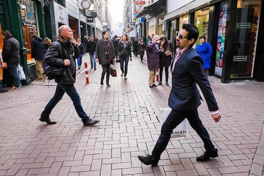 Nederland, Amsterdam, 19 maart 2015<br /> Winkelstraat Kalverstraat hoek Heiligeweg. Shoppende mensen. Modieuse man in designpak.<br /> <br /> Foto: Michiel Wijnbergh