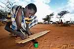 Abden Barl Keinan, 15, writes out verses from the Koran during an Islamic class in the Dadaab refugee camp in northeastern Kenya. He is among tens of thousands of newly arrived Somalis who have swelled the population of what was already the world's largest refugee camp.