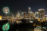 Exploding fireworks sprayed from the downtown Austin skyline with beautiful reflection on Lady Bird Lake as the world ushers in the New Year in Austin, Texas.