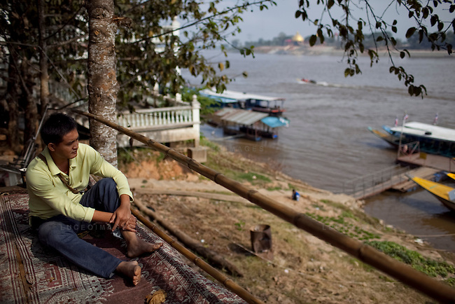 Pornlert Prompanya, 32, looks across the Mekong River to Laos while sitting outside his boat touring company in Sop Ruak, Thailand. A new casino that has opened in Laos is changing the shape of the waterfront. Photo taken on Thursday, December 10, 2009. Kevin German / Luceo Images