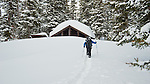 backcountry skiier with backpack skiing up to snow coverd cabin in glacier national park, montana