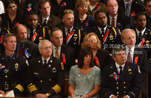 United States Senators Jon Corzine (Democrat of New Jersey), Chuck Schumer (Democrat of New York) and Joe Lieberman (Democrat of Connecticut) sit among the police and firemen attending the National Prayer Service at the Washington National Cathedral in Washington, D.C. on Friday, September 14, 2001..Credit: Ron Sachs / CNP