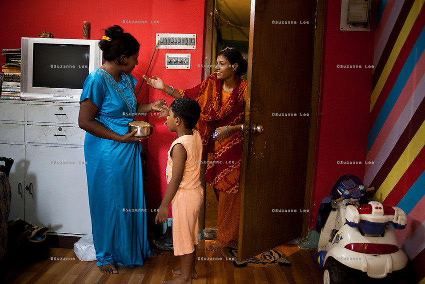 A neighbour brings some food over to Razia Shabnam (in blue) as she prepares lunch for her son at home in Ekbalpore, Calcutta, West Bengal, India. Razia Shabnam, 28, was one of the first women boxers in Kolkata. She was also the first woman in her community to go to college. She is now a coach and one of only three international female boxing referees in India.  Photo by Suzanne Lee for Panos London