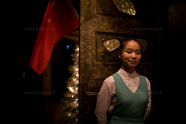 A restaurant employee greets tourists at the door in downtown Beijing, China on Monday, August 11, 2008.  Kevin German