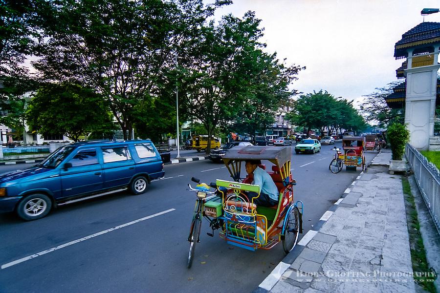 Indonesia, Sumatra. Medan. Some of the many becaks in Medan, outside Maimoun Palace.