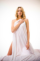 Blonde woman draped in bedsheet .