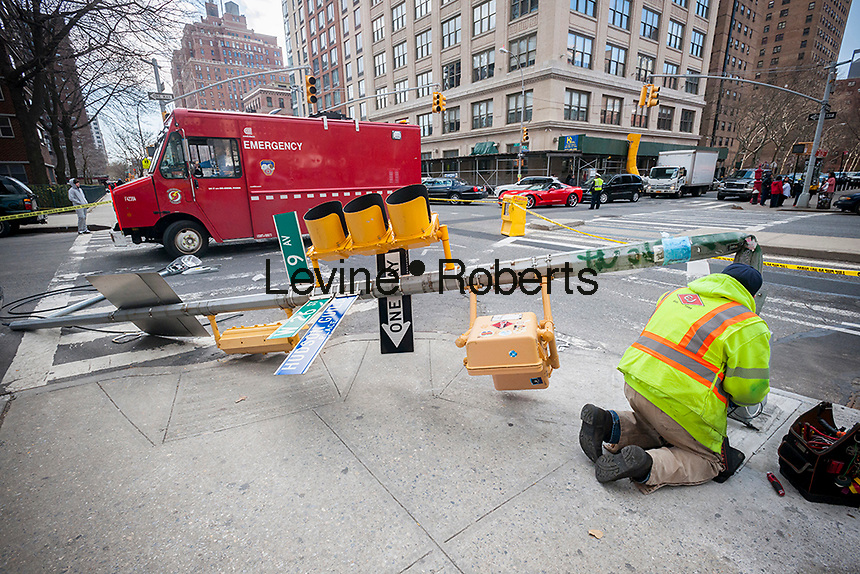 A worker for the New York City Dept. of Transportation works on the wiring in the base of a traffic light pole that was knocked over by a turning truck in New York on Saturday, March 26, 2016. (© Richard B. Levine)