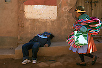 A villager passed out in the streets of Macha during the Tinku Festival. Macha, Bolivia, 4th May 2010, Photo Tim Clayton ...Each May, up to 3000 thousands indigenous Bolivian indians descend on the isolated mountainous village of Macha 75 miles north of Potosi in the Bolivian Andes. The 600 year old pre-hispanic Bolivia Festival of Tinku sees villagers from all over the region march into town to be pitted against each other in a toe to toe fist to fist combat.. They dance and sing in traditional costume and drink 96% proof alcohol along with chicha, a fermented beverage made from corn. Townspeople and sometimes the police oversee proceedings who often use tear gas to try and control the villages, whipped into a fighting frenzy by the dancing and alcohol, but as the fiesta goes on things often escalate beyond their control, with pitched battles between rival villages break out,  The blood spilt is an offering to the earth goddess - Pachamama - to ensure a good harvest for the coming year. Over the years dozens have died, yet the rite continues.