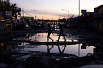 QUEENS, NY -- OCTOBER 22, 2013:  Pedestrians walk around the puddle-filled potholes on Willets Point Blvd in Willets Point on October 22, 2013 in Queens.  Photographer: Michael Nagle for The New York Times