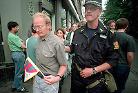 People wearing yellow T-shirts with the Chinese characters ?Human Rights? and weaving Tibetan flags were kept far away from president Jiang Zemin and his entourage of armed Chinese security personnel., during his visit to Oslo late June 1996. ..There was scathing editorial  criticism of the police silencing of all demonstrations in Oslo during Chinese president Jiang Zemin's official visit.  Minister of Justice Ms. Grete Faremo stated at a press conference that the right to demonstrate is fundamental and cannot be overruled, thus severely criticizing Oslo Chief of Police, Ms. Ingelin Killengreen. Prime Minister, Ms. Gro Harlem Brundtland also stated yesterday that she was ?far from happy? at the deployment of police to shield China's president from seeing demonstrators. ..Later, Chief of Police apologized to Palden Gyatso, the 65 year old monk who escaped from Tibet after spending 33 years in jail, for the police action against him.