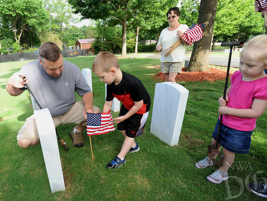 NWA Democrat-Gazette/ANDY SHUPE<br /> J.J. Spears (left) of Springdale watches as his son, James Spears, 6, places a flag Saturday, May 28, 2016, at the grave marker of James' great-grandmother, Carol Carter Wright, who served in the Navy during World War II, as James' grandmother, Gail McWhorter of Fayetteville and sister, Annabelle Spears, 3, watch at the Fayetteville National Cemetery. Volunteers placed flags in front of the approximately 8,700 grave markers at the facility ahead of the Memorial Day holiday. A service is planned for 10 a.m. Monday at the cemetery featuring Col. Bobbi Doorenbos, commander of Arkansas Air National Guard&rsquo;s 188th Wing.