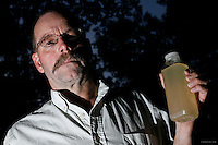 Craig Sautner of Dimock, PA, holds a bottle of his contaminated tap water collected in March 2010. Their water problems started in September 2008 after natural gas drilling on their property a month earlier. &quot;Our water smells of diesel fuel,&quot; says Sautner. &quot;In our water, we've found aluminum, manganese, chloride, iron, magnesium, sodium, strontium-T, all above the EPA limits, and TDS [Total Dissolved Solids] and other elements we can't disclose yet.&quot; <br />