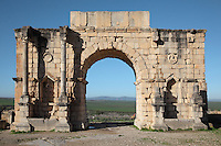 The Triumphal Arch of Caracalla, built 217 AD by the city's governor Marcus Aurelius Sebastenus at the end of the Decumanus Maximus in honour of Emperor Caracalla, 188-217 AD, and his mother Julia Domna, Volubilis, Northern Morocco. The arch was reconstructed 1930-34 and was originally topped with a bronze chariot pulled by 6 horses. The medallion busts are portraits of Caracalla and Julia Domna. Volubilis was founded in the 3rd century BC by the Phoenicians and was a Roman settlement from the 1st century AD. Volubilis was a thriving Roman olive growing town until 280 AD and was settled until the 11th century. The buildings were largely destroyed by an earthquake in the 18th century and have since been excavated and partly restored. Volubilis was listed as a UNESCO World Heritage Site in 1997. Picture by Manuel Cohen