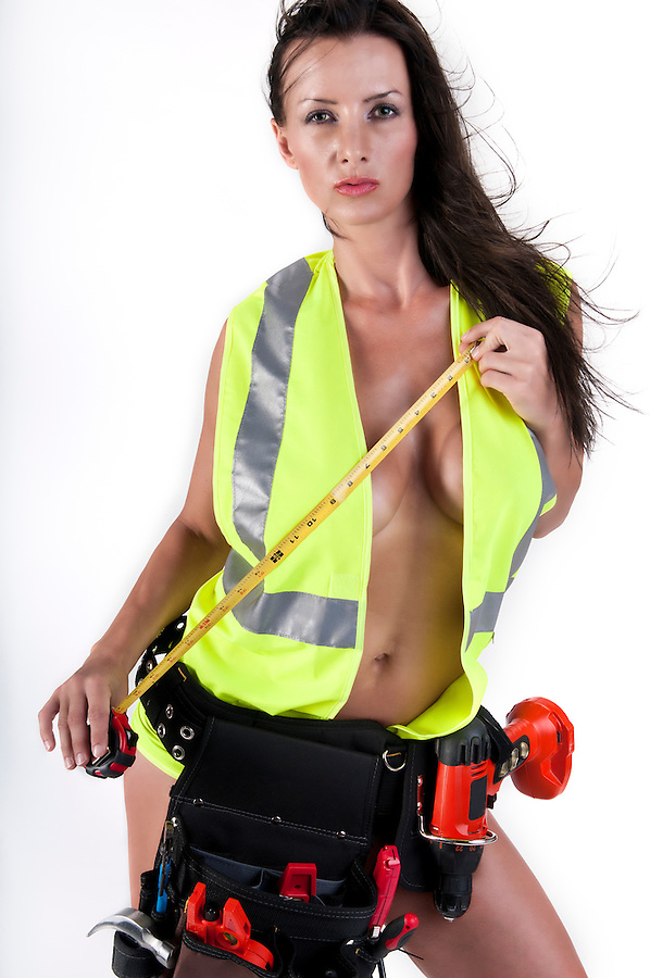 Very sensual woman with safety vest and too playing handyman. All logos removed.