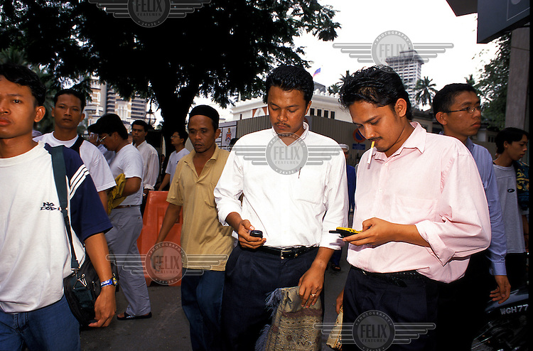 Worshippers light up cigarette and check their cellphone messages after finishing Friday Prayers outside Masjid Jamie, a huge mosque in central Kuala Lumpur, Malaysia.  Credit: Chris Stowers.