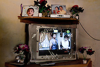"Photographs of Shardaben's pregnancy (right) and 2nd surrogacy baby are displayed atop the television set in her living room...Shardaben Kantiben, 31; Husband is Kantibhai Motibhai (37).3 children --- 2 girls -  Usha(15) and Lakshmi (18, in pink); 1 boy, Chintan (17).- Education costs for all three come to Rs. 15,000 per year.- Shardaben was a two-time surrogate. First time she gave birth to twin girls for a Taiwanese couple and the second time a boy for an Indian couple from America (photo on TV set because she's proud that it was a boy).- The second time she became emotional and they got a gold ring of Rs. 1,500 made for the boy, which they presented to the biological parents. They are not in touch with either couple..- From the two surrogacies, they earned a little over 700,000rupees..-200,000rupees will be given as dowry for Lakshmi's wedding..- They leased agricultural land (Rs. 2 lakhs for five years) which earns them Rs. 60,000-70,000 a year; they bought two buffaloes worth Rs. 60,000 and make almost 6000-7000 per month selling milk; they bought a motorbike for Rs. 25,000; they put some money into house repairs and the construction of toilets, and opened a fixed deposit in Shardaben's name for Rs. 1.5 lakh and one in the name of their son, Chintan, for Rs. 25,000..Quotes..""Everyone says they'll keep in touch and take down addresses and phone numbers but nobody looks back. And I guess it works well. Our main interest was in the money. Their main interest is in the baby."" - KantiBhai.""Their rules apply at the surrogate house. It does curtail the freedom. When I used to go, everybody would just be lying. They count the days when they can go back."" - Kantibhai.""Ours is natural birth but surrogacy is a man-made pregnancy. There's a lot of risk. She must have taken at least 300 injections."" - Kantibhai of his wife...The Akanksha Infertility Clinic is known internationally for its surrogacy program and currently has over a hundred surrogate mothers pregnant in their"