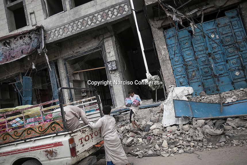 Wednesday 15 July, 2015: Civilians carry out goods from a house building damaged by a bomb blast in one downtown of Sa'dah, a city subdued to heavy bombarments carried out by the Saudi-led coalition in the northern province of Sa'dah, the stronghold of the Houthi's movement in Yemen. (Photo/Narciso Contreras)