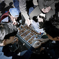 Afghan refugees taking boiled eggs in a refugee camp in Patras. Patras is home to about 3,000 illegal immigrants. Most of them are Afghans, although there are also some Iranians and Uzbeks. They stop in Patras to try and find passage to various European destinations by hiding in ships, containers and trucks parked in the port. If they are lucky they will make it to their destination. Many of them live in shacks made from cartons, plastic and wood they found on the beach. To shelter from the cold they also squat in abandoned buildings, living without water and electricity. The living conditions are inhumane and unhygienic.
