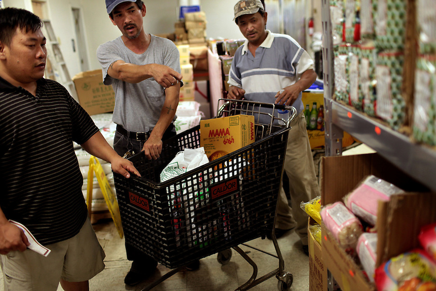 Shrimpboat captain Minh Vo, left, with his deckhands Cao Dang and Phong Nguyen, right, carefully spend the $100 grocery check provided by Catholic Charities after waiting for over four hours for financial support in New Orleans East, LA on May 21, 2010. The Vietnamese fishing community have struggled to survive after the shrimping industry shut down three weeks earlier after the BP oil spill in the Gulf of Mexico.