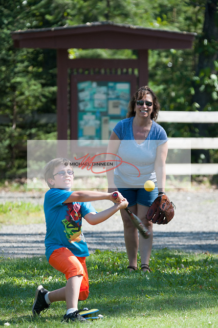 An afternoon at the Eagle River campground turned into a batting session for eight-year-old Mason Roberson as his mother Marti plays catcher. Satturday afternoon. Roberson said that in her youth her family spent many occasions at the campground adjacent to Eagle River.  Photo for the Star by Michael DInneen