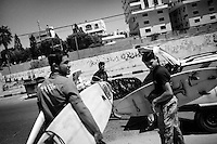 Surfers load a taxi with surfboards as they prepare to catch waves off Gaza City, in the Gaza Strip.