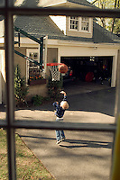 Boy shooting baskets in the driveway.
