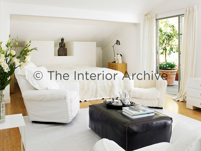 A spacious white bedroom with a seating area with a bamboo floor. Armchairs are placed around a black leather ottoman on a white leather rug.