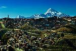 Snowcapped Mt Huayna Potosi rises above the canyon rim and hillside houses of La Paz.