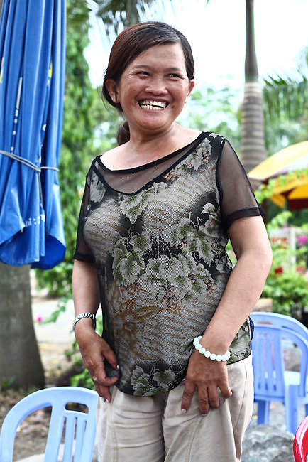 "Nguyen Thi Dung, 45, grins for a photograph near her drink stand in Da Nang, Vietnam. Dung's father was a soldier for the South Vietnamese army during the Vietnam War and died at 62 from complications related to Agent Orange exposure. She and an older brother were born with hip dysplasia that doctors say is linked to their father's exposure, and she suffers from neurological damage that causes one side of her mouth to droop and for her eyes and mouth to twitch uncontrollably. ""My son's condition is even worse,"" she says. ""There are three generations in my family like this, and the doctors say that for all three generations, our condition is because of Agent Orange."" The family survives partially on about $25 that each gets monthly from the Da Nang Association of Victims of Agent Orange/Dioxin, an aid group. The Vietnam Red Cross estimates that 3 million Vietnamese suffer from illnesses related to dioxin exposure, including at least 150,000 people born with severe birth defects since the end of the war. The U.S. government is paying  to clean up dioxin-contaminated soil at the Da Nang airport, which served as a major U.S. base during the conflict. But the U.S. government still denies that dioxin is to blame for widespread health problems in Vietnam and has never provided any money specifically to help the country's Agent Orange victims. May 30, 2012."