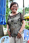 Nguyen Thi Dung, 45, grins for a photograph near her drink stand in Da Nang, Vietnam. Dung's father was a soldier for the South Vietnamese army during the Vietnam War and died at 62 from complications related to Agent Orange exposure. She and an older brother were born with hip dysplasia that doctors say is linked to their father's exposure, and she suffers from neurological damage that causes one side of her mouth to droop and for her eyes and mouth to twitch uncontrollably. &quot;My son's condition is even worse,&quot; she says. &quot;There are three generations in my family like this, and the doctors say that for all three generations, our condition is because of Agent Orange.&quot; The family survives partially on about $25 that each gets monthly from the Da Nang Association of Victims of Agent Orange/Dioxin, an aid group. The Vietnam Red Cross estimates that 3 million Vietnamese suffer from illnesses related to dioxin exposure, including at least 150,000 people born with severe birth defects since the end of the war. The U.S. government is paying  to clean up dioxin-contaminated soil at the Da Nang airport, which served as a major U.S. base during the conflict. But the U.S. government still denies that dioxin is to blame for widespread health problems in Vietnam and has never provided any money specifically to help the country's Agent Orange victims. May 30, 2012.
