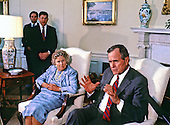 United States President George H.W. Bush speaks to the press pool as his mother, Dorothy Walker Bush, 87, looks on in the Oval Office of the White House in Washington, D.C. during his first full day as President on January 21, 1989. White House Chief of Staff John Sununu stands in the back at left.<br /> Credit: Dennis Brack / Pool via CNP