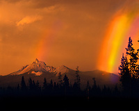 Evening sun and passing rainstorm creates double rainbow over Mt. Thielsen