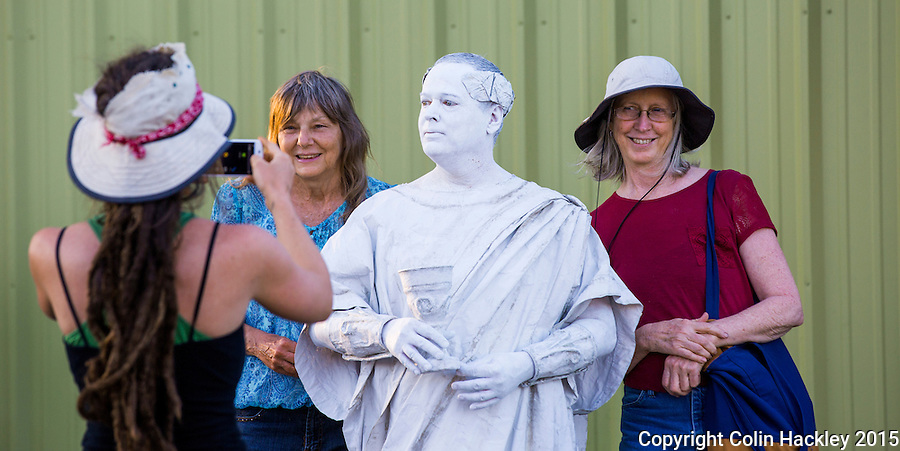 Paul Wilford portrays a sculpture of Ceasar and attracts Mary Allgire, left, and Jessie King for a photo during First Friday in Tallahassee's Railroad Square.<br /> <br /> COLIN HACKLEY PHOTO