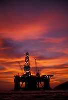 Petroleum platform in the sea silhouetted by the sunset. Economic development. Brazil.