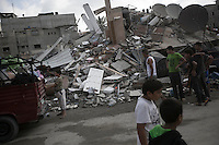 "August 23, 2014 - Gaza City, Gaza strip, Palestinian Territory: Palestinian civilians walk by a house building destroyed as residents collect their goods from the rubble after the building was targeted by an airstrike in the Sabra neighborhood of Gaza City while ""Protective Edge"" Israeli military operation continues in the Gaza strip. (Narciso Contreras/Polaris)"