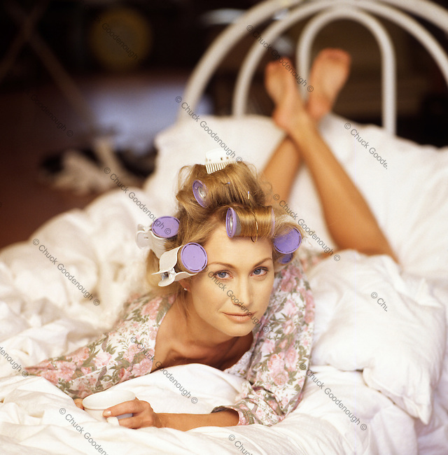Stock Photo of Blond Woman in Curlers with Coffee Cup Lying on a Bed