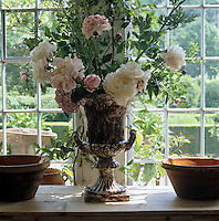 Peonies and hydrangeas cut from the garden are arranged in a stone urn