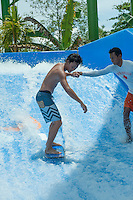 Yujiro getting a hand on his first attempt on a static wave.<br /> Kuta, Bali
