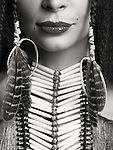 Artistic closeup portrait of a woman wearing aboriginal native accessories necklace and feathers in her hair. Close up of lips. Black and white.