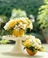 Half grapefruits filled with white freesias and yellow roses are used as centre pieces on this table