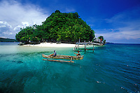 Locals with a boat at a white sand beach on a lush tropical island, Mindanao, Philippines