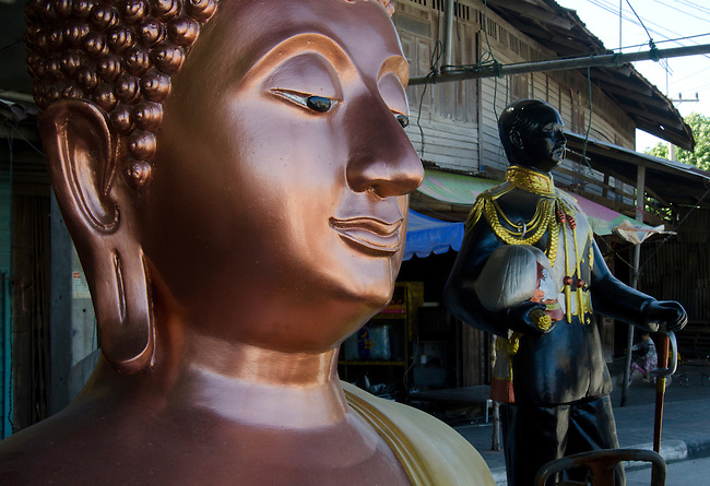 Bronze Sukhothai style Buddha statue with King Chulalogkorn in background.