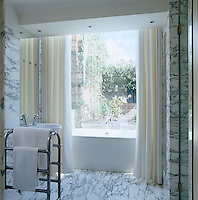 The marble-lined bathroom opens onto a small roof terrace and the bath is enclosed in a glass box