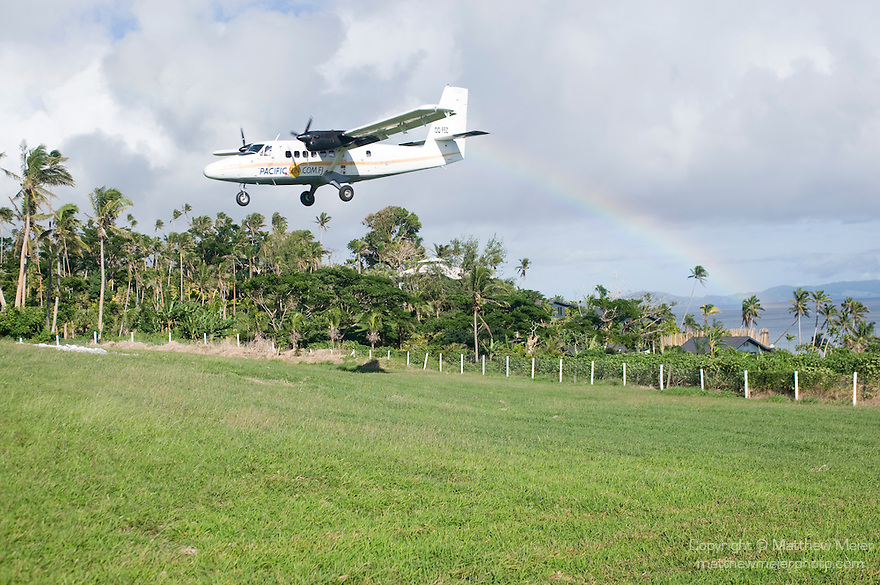 Matei Airport, Taveuni, Fiji;  a rainbow touches the horizon in the background as a De Havilland DHC-6 Twin Otter airplane, owned and operated by Pacific Sun Airlines, comes in for a landing at the Matei Airport, the twin engine, propeller powered plane holds 14-16 passengers