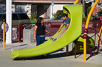 Two children using the slide play structure at Circle Park, a pocket park located on Park Circle Drive in Anaheim, California.  A boy is about to go down the slide, while a girl next to him holds a football and dog leash.